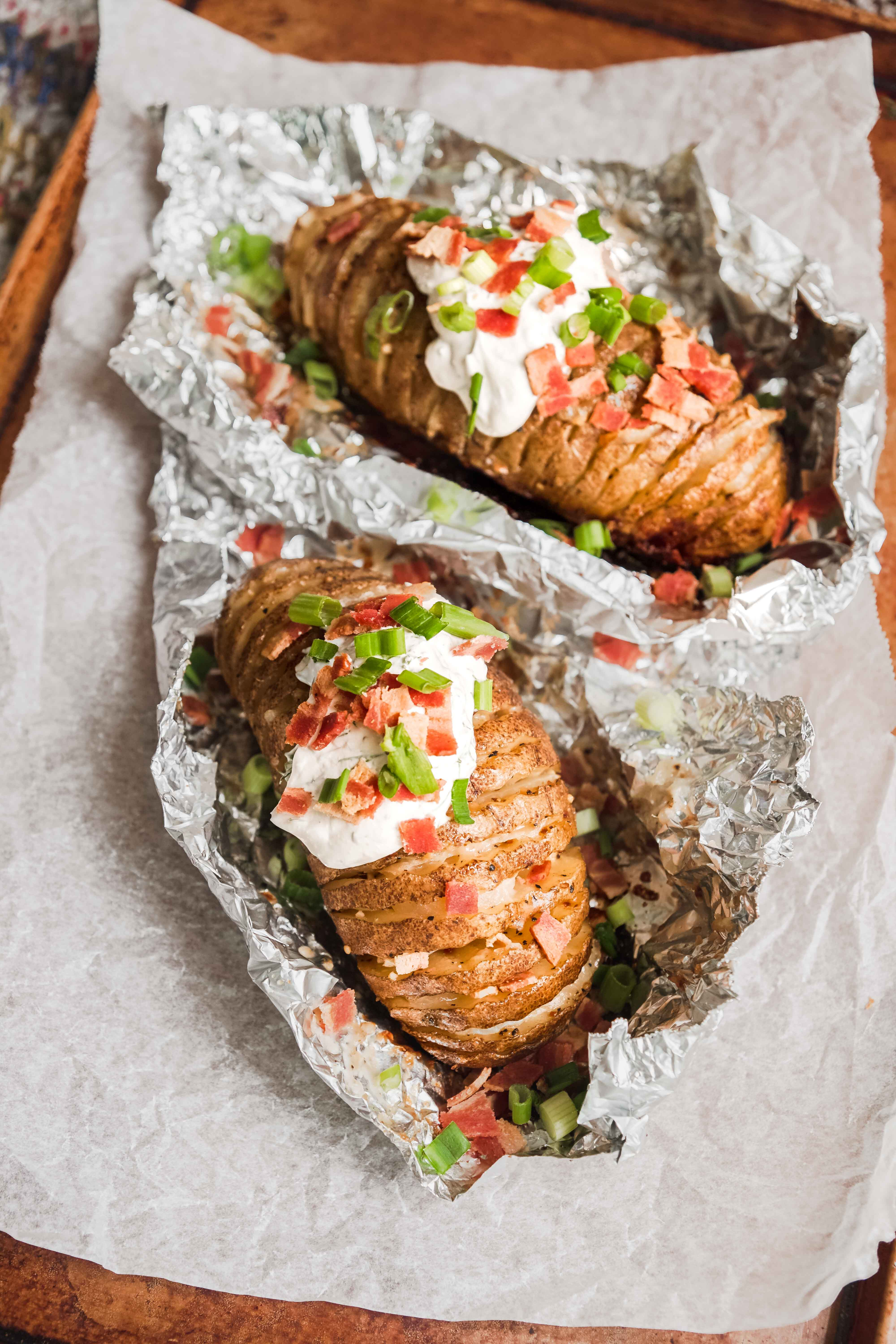 grilled hasselback potatoes with sour cream in tin foil