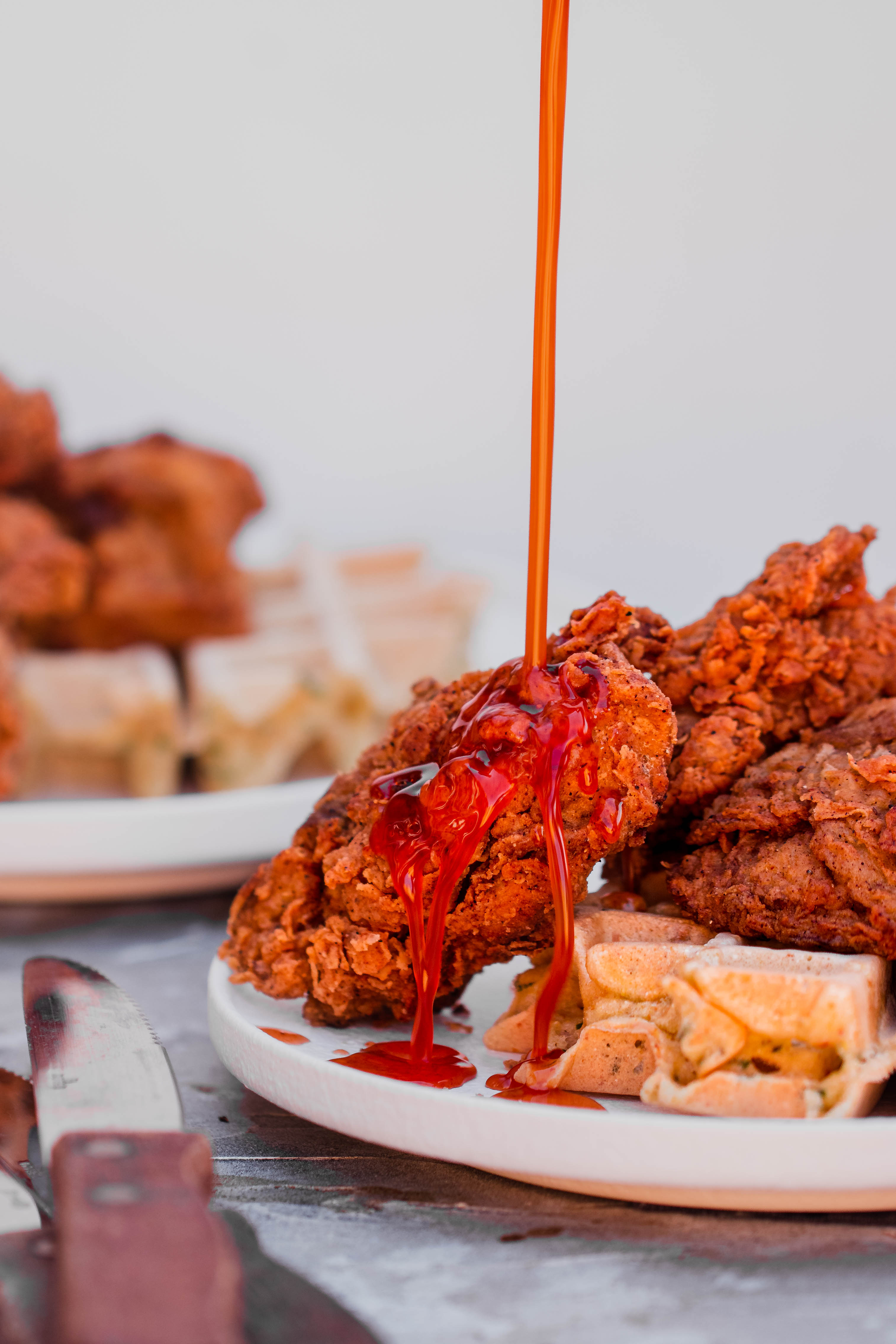 cayenne maple syrup drizzling over vegan chicken and waffles