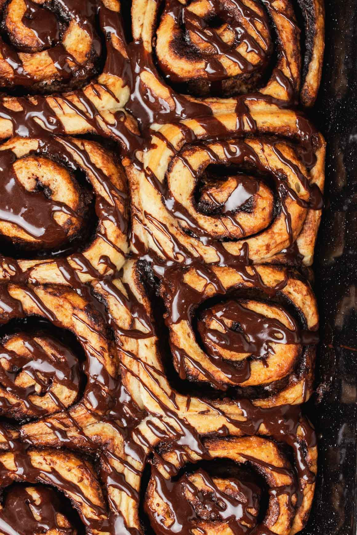 baking dish with chocolate cinnamon rolls topped with chocolate glaze