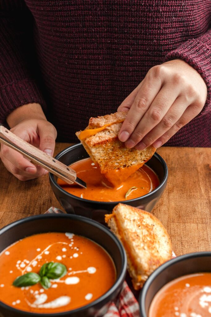 grilled cheese being dunked in creamy tomato soup
