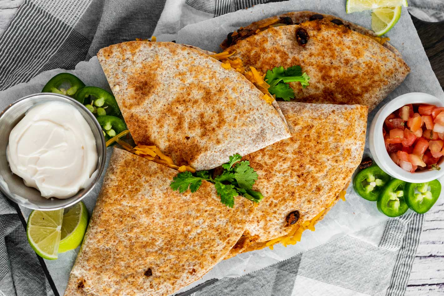 Top-down image of a golden brown black bean quesadilla cute into quarters on a white board on a grey kitchen napkin. To the side there is a small bowl of diced tomato, sliced jalapeno and another bowl of vegan sour cream.
