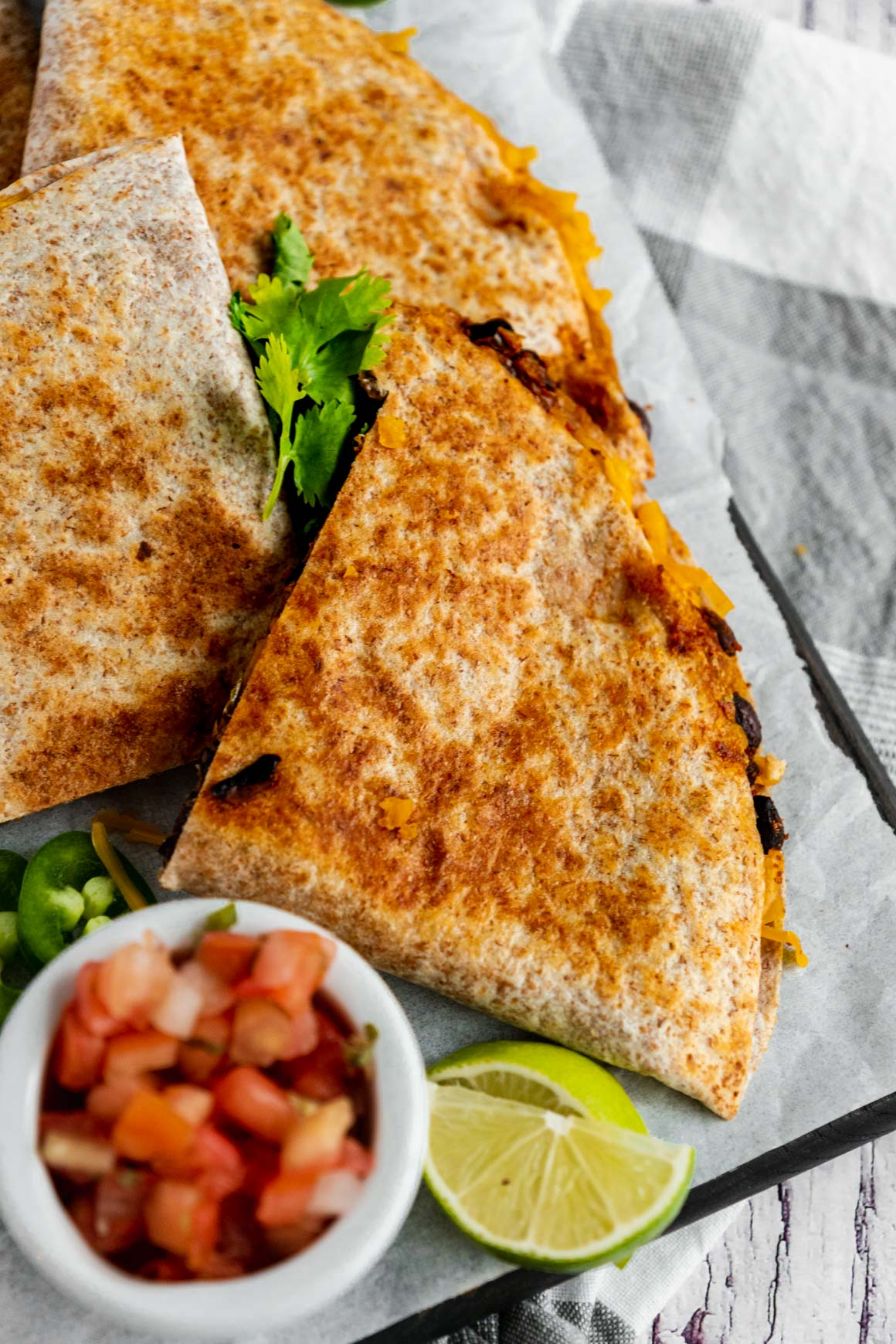 Side-view image of a golden brown black bean quesadilla cute into quarters on a white board on a grey kitchen napkin. To the side there is a small bowl of diced tomato, sliced jalapeno and another bowl of vegan sour cream.