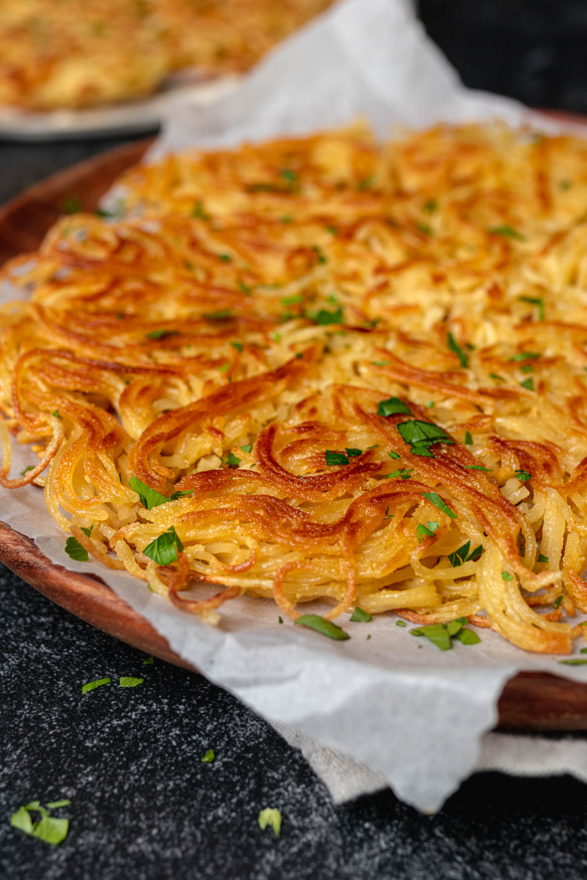 Side shot of a vermicelli omlette that is golden brown and sprinkled with parsley on a piece of parchment on a wood plate. You can see a second one blurry in the background.