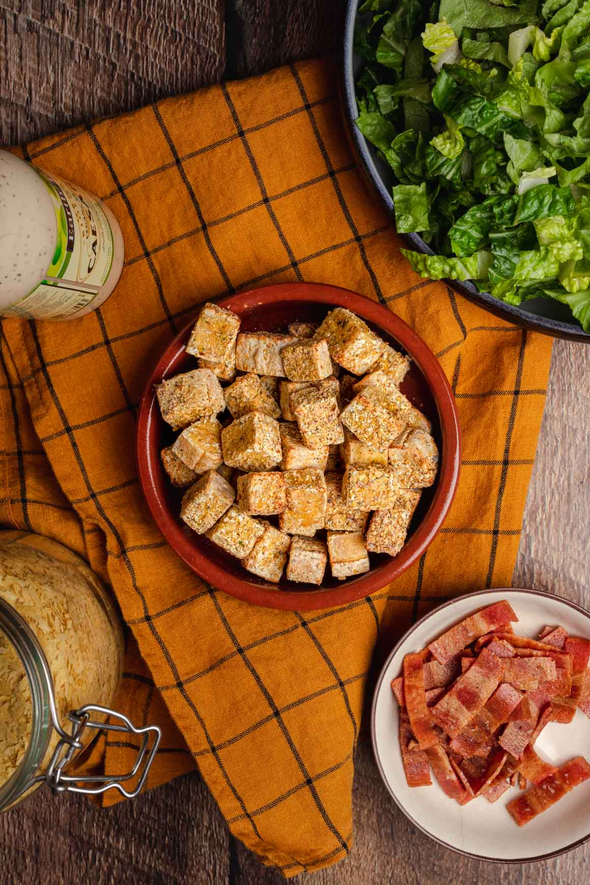 Top down shot of a bowl fo crispy tofu cubes with a yellow cloth underneath. In the corners of the image you can see a bowl of shredded iceberg lettuce, a bowl of crispy vegan bacon, a jar of nutritional yeast, and a bottle of vegan caesar dressing.