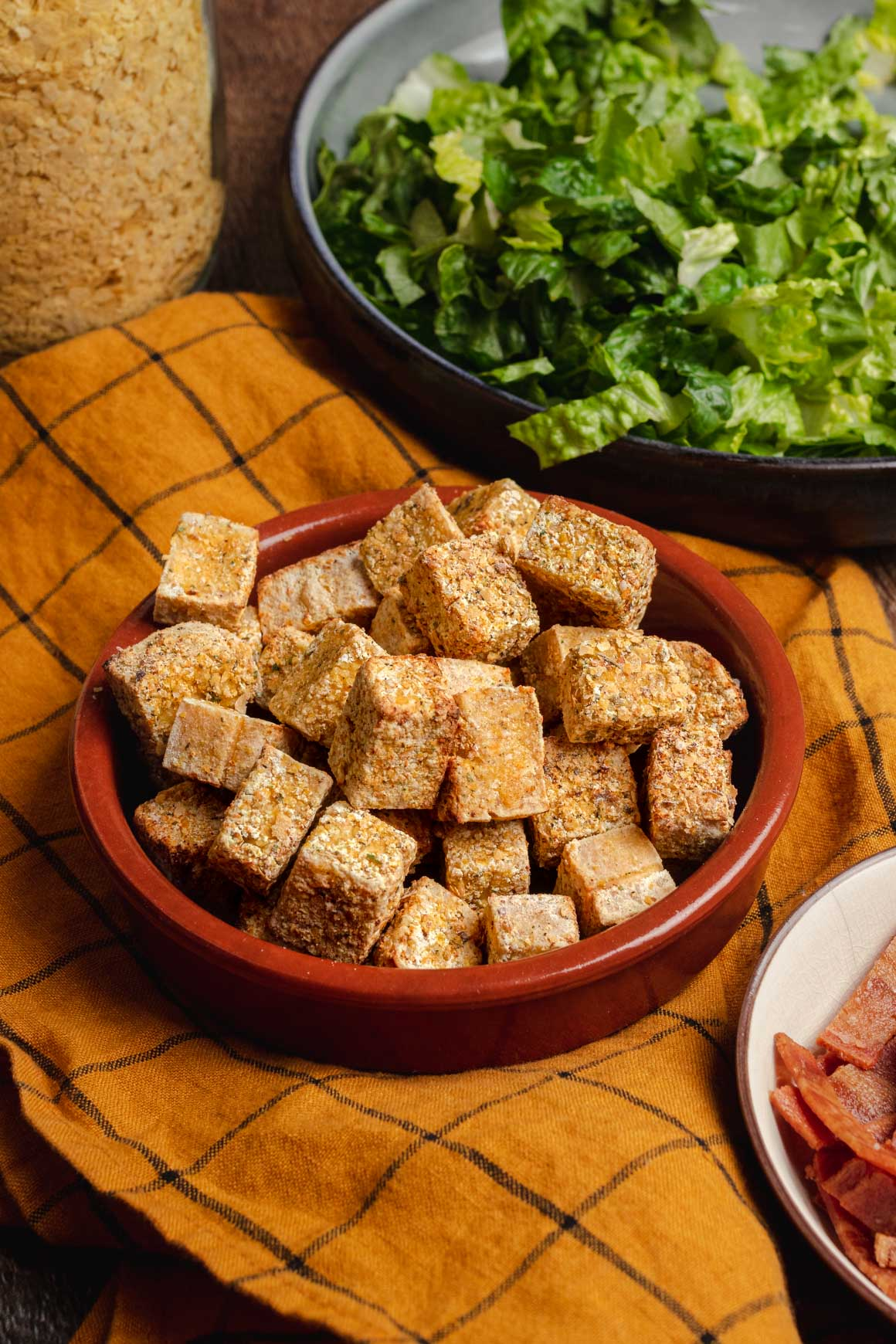 Side view shot of a bowl of crispy tofu cubes with a yellow cloth underneath. In the corners of the image you can see a bowl of shredded iceberg lettuce, a bowl of crispy vegan bacon, and a jar of nutritional yeast.
