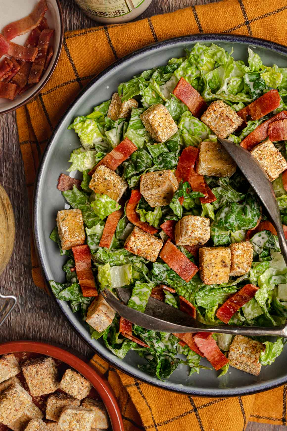 Top down shot of a shallow blue bowl with vegan caesar salad with vegan bacon strips and herby crispy tofu croutons on top of a yellow cloth.