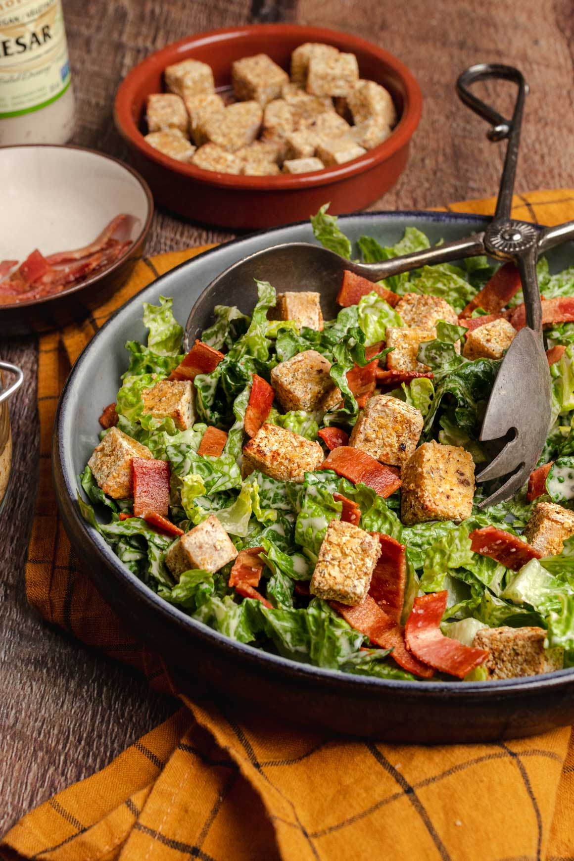 Side view of a blue shallow bowl of vegan caesar salad with crispy tofu croutons and vegan bacon. Bahind you can see a bowl of additional tofu croutons, a bowl of bacon and a bottle of caesar dressing.