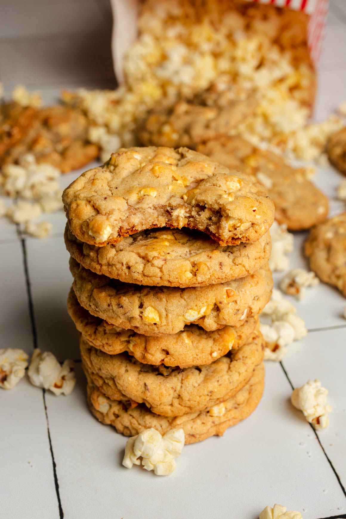 Stack of cookies, with the top one that has a bite out of it. A bag of popcorn is spilling out in the background.