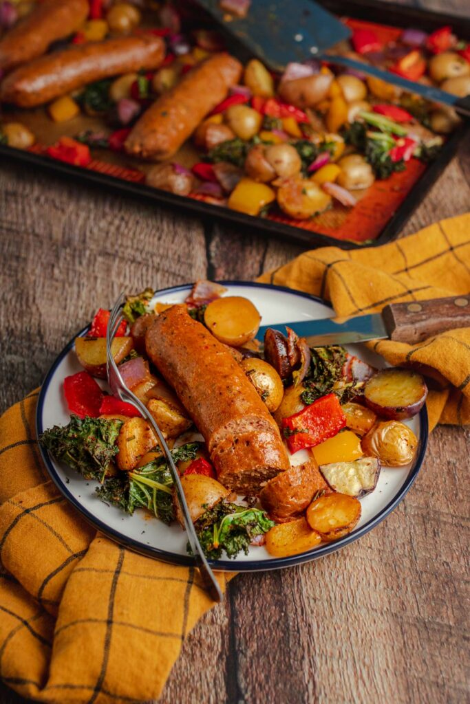 Top down shot of vegan sausage sheet pan dinner on a white plate, on top of a yellow linen. With a dark sheet pan peeking in the top of the frame; with roasted bell peppers, baked baby potatoes, crispy kale, and red onion, with beyond sausage on top.