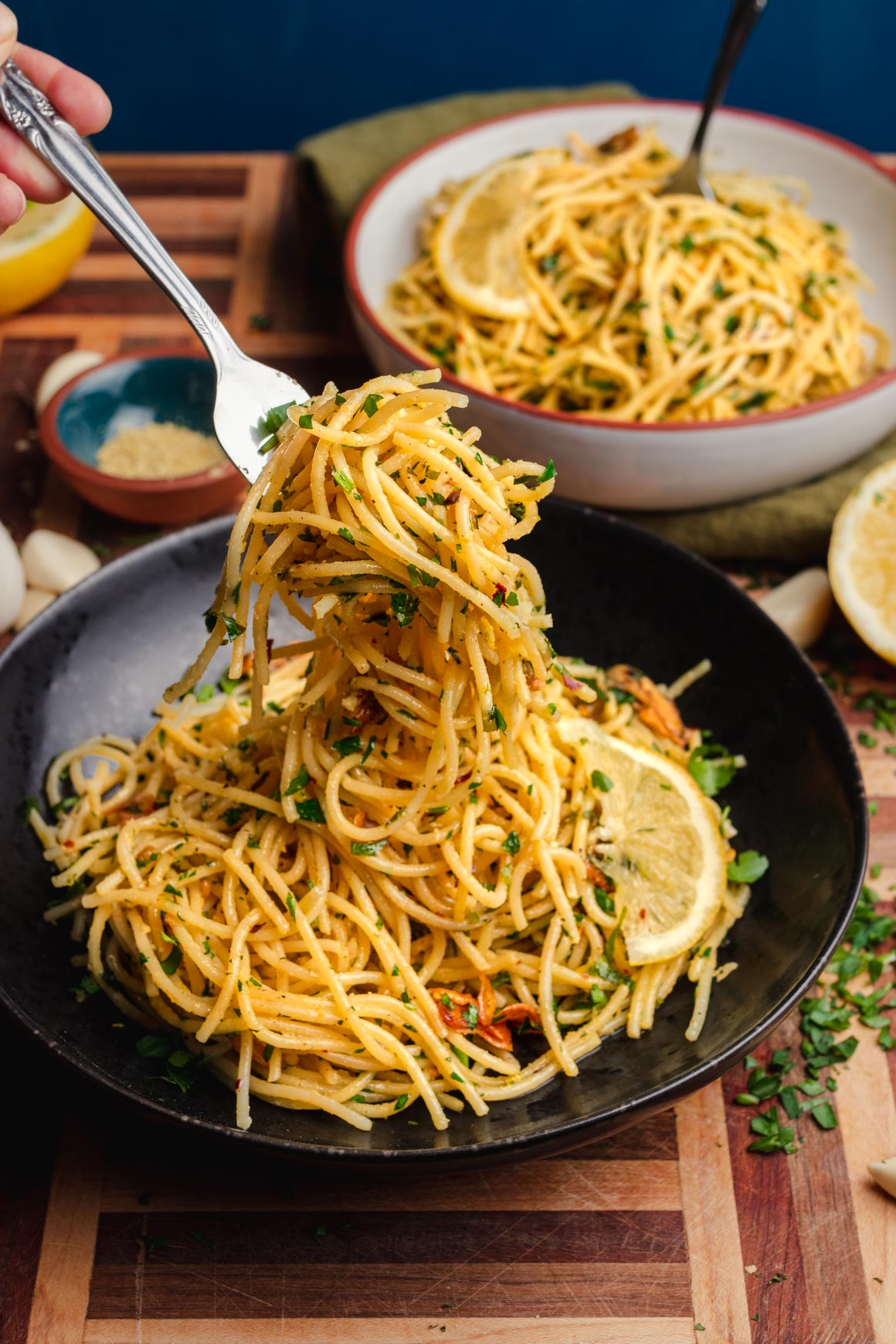 bowl of Scarlett's Pasta on a wooden board with minced parsley, garlic cloves and lemon wedges