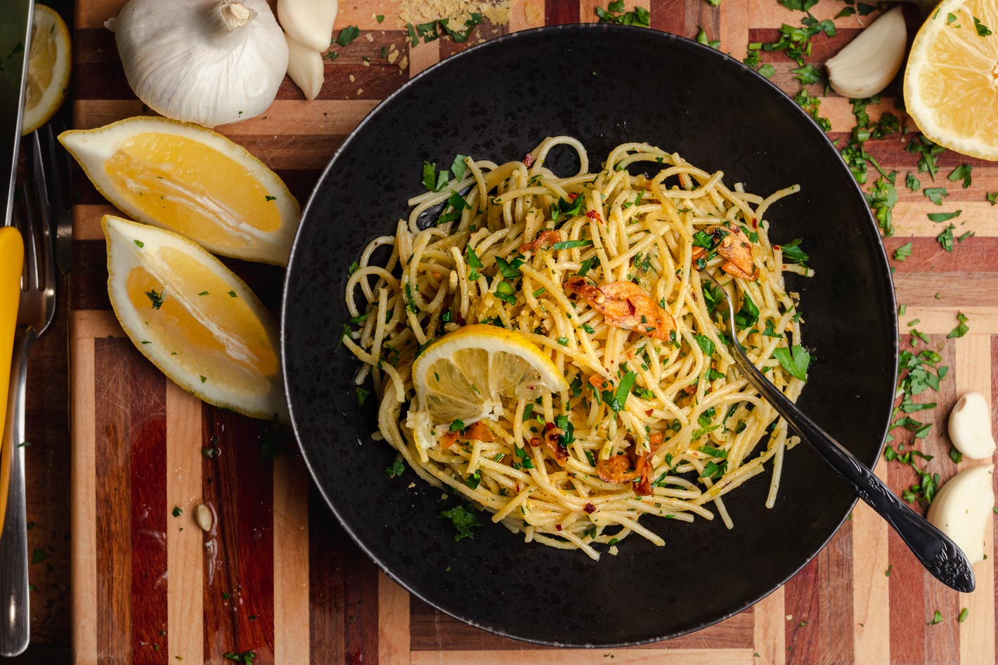 bowl of pasta aglio e olio on a wooden board with minced parsley, garlic cloves and lemon wedges
