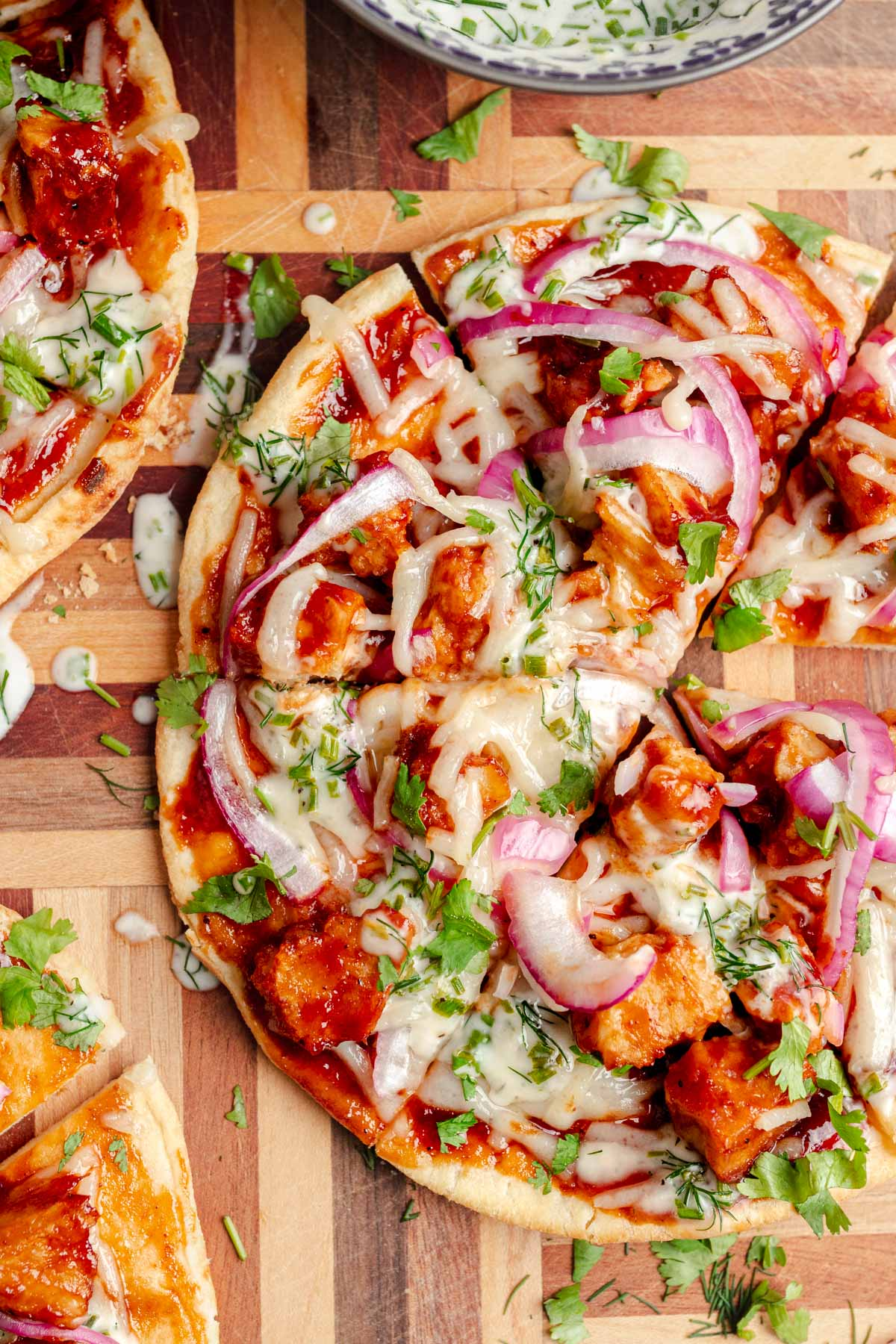 top down picture of a pita with vegan bbq chicken, vegan cheese, red onion, cilantro and drizzled with vegan ranch